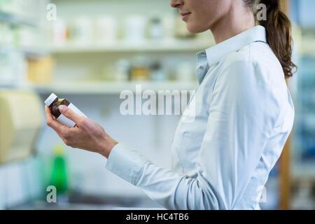Pharmacien de vérifier une bouteille de médicament en pharmacie Banque D'Images