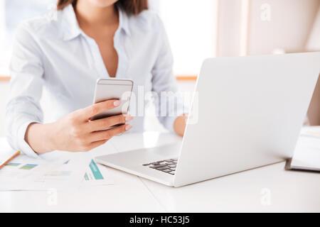 Portrait of young businesswoman habillé en chemise blanche assis dans son bureau et la tenue de téléphone cellulaire.