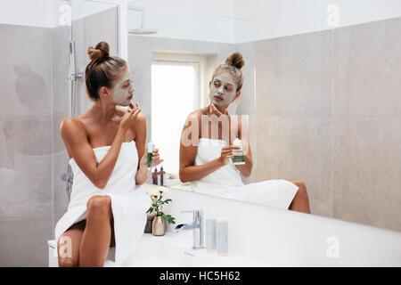 Jeune femme l'application de boue pour le visage masque argile à son visage dans la salle de bains. Belle femme Banque D'Images