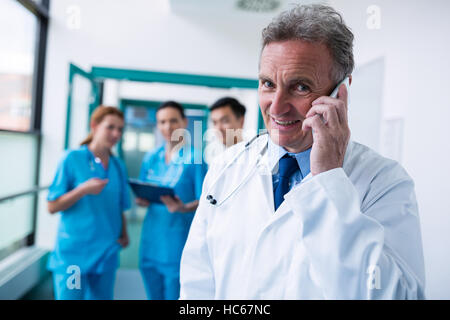 Portrait of smiling doctor talking on mobile phone in corridor Banque D'Images