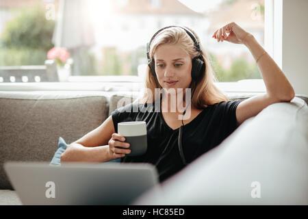 Belle jeune femme avec un casque tenant une tasse de café et à la recherche à l'ordinateur portable. Femme assise Banque D'Images