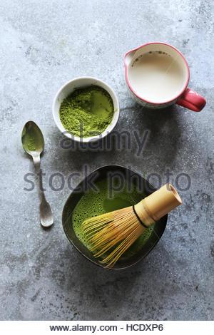 La préparation du thé vert matcha latte.en poudre dans un bol et le lait de coco dans une tasse.vue d'en haut Banque D'Images