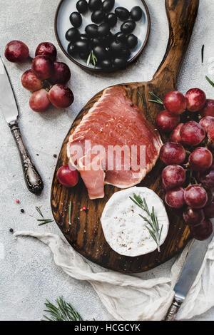 Assorted antipasti italiens des collations pour un dîner avec vin ou de travail sur planche à découper en bois. Banque D'Images