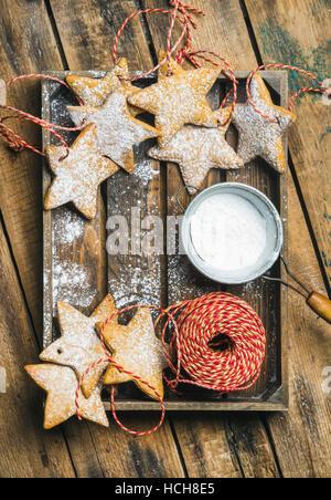 Gingerbread cookies en forme d'étoile de Noël avec du sucre en poudre et la décoration de corde en plateau en bois Banque D'Images