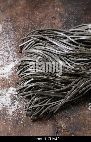 Noir d'encre de seiche crus crus pâtes spaghetti à la farine sur fond de bois sombre. Vue de dessus avec l'espace Banque D'Images