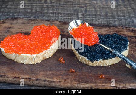 Sandwiches avec caviar en forme de coeur sur une planche à découper en bois et l'arrière-plan. Banque D'Images