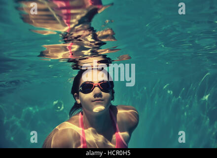 Girl swimming underwater in piscine. Banque D'Images