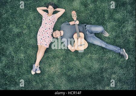 Jeune homme jouant de la guitare à sa copine dans la nature - rencontres couple Banque D'Images
