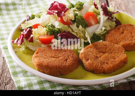 Les escalopes et carottes salade de chicorée, le chou et les tomates sur une plaque horizontale. Banque D'Images