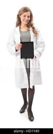 Jeune femme en sarrau blanc holding tablet Ordinateur avec écran face à l'appareil photo pleine longueur, isolé Banque D'Images