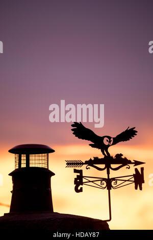 Une silhouette d'Owl et souris girouette et pot de cheminée contre une soirée spectaculaire coucher du soleil dans Banque D'Images