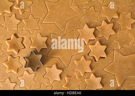 Gingerbread cookie dough à découper en forme d'étoiles à l'emporte-pièce et les cookies. Arrière-plan de l'alimentation, Banque D'Images