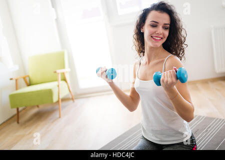 Belle femme sportive exerçant à la maison pour rester en forme Banque D'Images