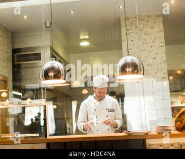 Jeune chef avec uniforme blanc debout à une cuisine moderne dans le restaurant et la préparation des aliments Banque D'Images