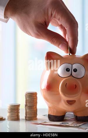 Concept épargne avec la main de l'homme mettant l'argent dans tirelire laughing blanche réfléchissante sur une table Banque D'Images