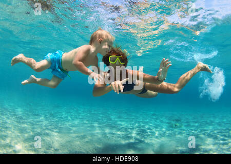Famille heureuse. Mère avec fils bébé sous l'eau à la piscine de plongée la mer. Mode de vie sain, actif, parent, Banque D'Images