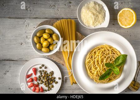Spaghetti crus et cuits avec différents sur l'entrée Vue de dessus de table en bois blanc. Concept de cuisine italienne Banque D'Images