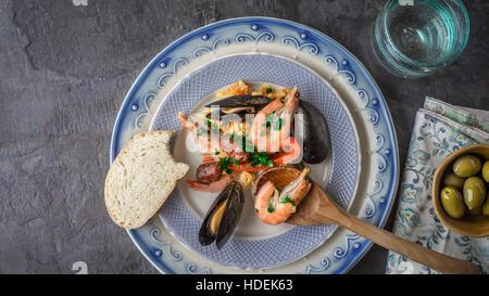 La plaque avec la paella sur la table en pierre sombre avec différents accessoires vue d'en haut Banque D'Images