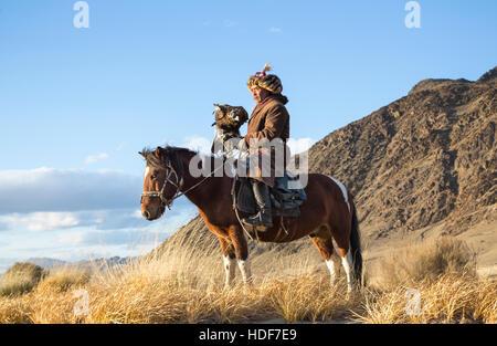 Bayan Ulgii, la Mongolie, le 2 octobre, 2015: Old eagle hunter avec son aigle d'Altaï sur son cheval Banque D'Images