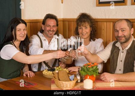 Deux couples habillés en vêtements traditionnels assis à une table, tintement des verres à vin Banque D'Images