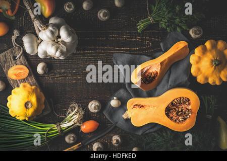 Potiron avec différents légumes sur la vieille table en bois Banque D'Images