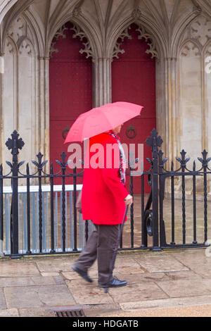 Winchester, Hampshire, Royaume-Uni 12 décembre 2016. Lady se dépêche le long passé de la rue la cathédrale de Winchester en essayant de garder sec sous parapluie rouge sur un jour de bruine humide à la Winchester en décembre. Credit: Carolyn Jenkins/Alamy Live News