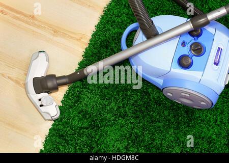 Aspirateur position sur tapis vert Banque D'Images