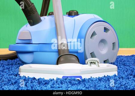 Aspirateur puissant debout sur la moquette bleue. Banque D'Images