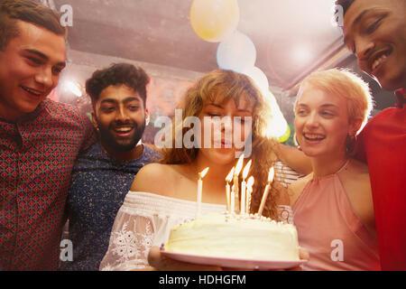 Woman blowing candles tout en célébrant l'anniversaire avec des amis à la cour Banque D'Images