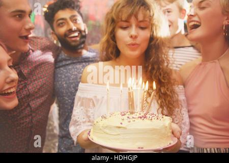 Woman blowing candles tout en célébrant l'anniversaire avec des amis Banque D'Images