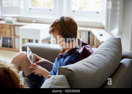 Une maison de famille. Un garçon sur un canapé, à l'aide d'une tablette numérique, portant des écouteurs. Banque D'Images
