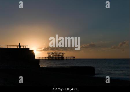 Figure silhouetté contre soleil levant derrière épi, l'abandon de Brighton West Pier en arrière-plan Banque D'Images
