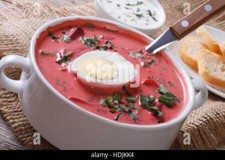 Soupe de betterave rouge délicieux avec des œufs et de la crème sure close-up dans un bol blanc horizontal. Banque D'Images