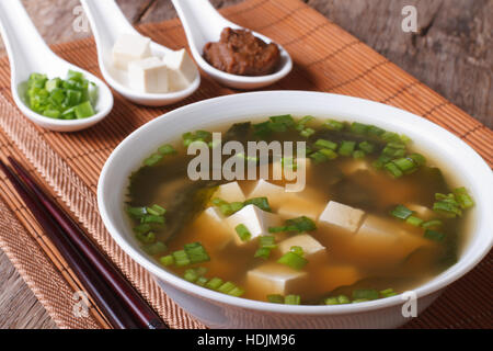 La soupe miso japonaise dans un bol blanc et ingrédients dans une cuillère sur une table horizontale de près. Banque D'Images