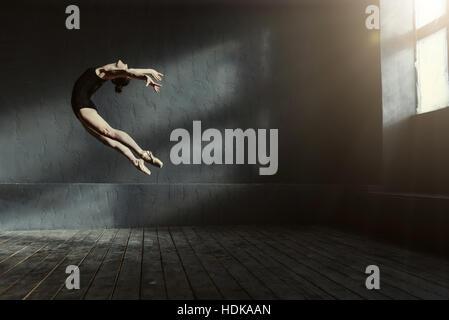 Danseur de ballet professionnel effectuant dans l'obscurité éclairée prix Banque D'Images
