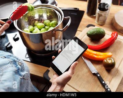 Dans la cuisine femme lisant une recette à partir de l'iPhone 7 dans sa main Banque D'Images