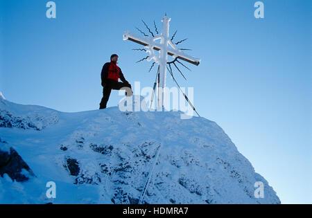 Homme debout à côté du sommet cross sur Mt. Steinerner Jaeger, pré-Alpes près de Reichraming en hiver, Haute Autriche, Banque D'Images