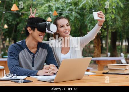 Cheerful young couple à l'aide de lunettes de réalité virtuelle et de décisions avec selfies smartphone outdoors Banque D'Images