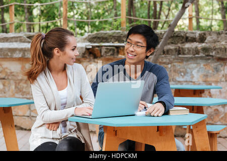 Happy young couple talking and using laptop outdoors Banque D'Images