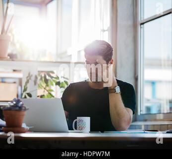 Jeune homme d'affaires avec le stress en regardant son ordinateur portable au bureau. Homme de la concentration Banque D'Images
