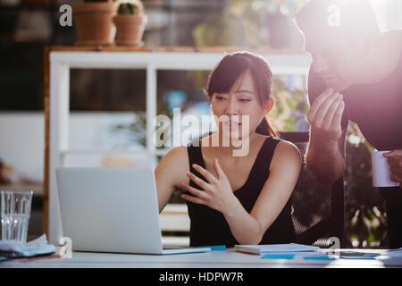 Photo de deux jeunes collègues d'affaires à la recherche à l'ordinateur portable. Businesspeople working together on laptop in office.