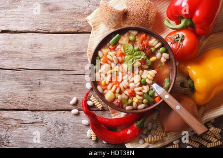 L'Italien minestrone de légumes dans un bol et les ingrédients sur la table horizontale vue du dessus. Banque D'Images
