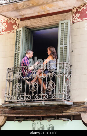 Un couple sur un balcon à Barcelone, Espagne avec l'homme des messages sur son smartphone et la femme à la recherche Banque D'Images