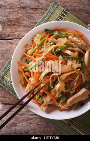 Chow mein: nouilles frites avec du poulet et légumes close-up vertical Vue de dessus. Banque D'Images