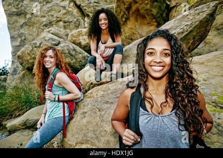 Smiling des femmes portant des sacs à dos près de rock formation Banque D'Images