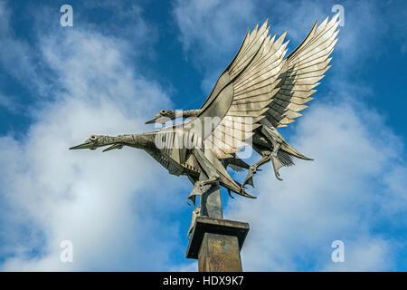 Statue, ou coulage de métaux, de trois canards colverts en vol sur les rives de la rivière Wye à Ross on Wye, Herefordshire en Angleterre
