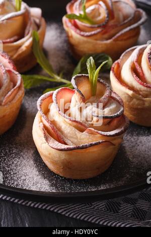 L'alimentation saine: apple pie sous la forme de roses sur une plaque noire verticale de macro.