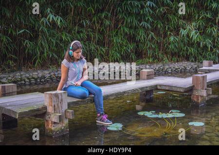 Fille à écouter la musique au casque dans le parc Banque D'Images