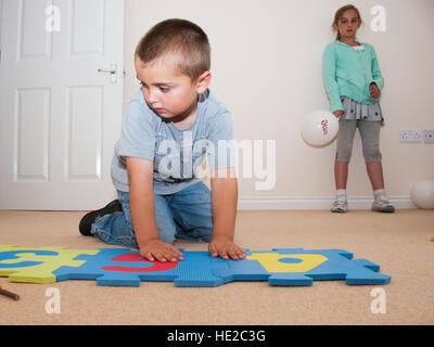 S'installer en famille à nouveau à la maison après avoir été relogés par Housing Association Banque D'Images