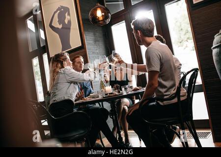 Groupe d'amis au restaurant of beer. Jeune homme et femme assis à table et le grillage des boissons au café. Banque D'Images